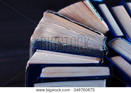 Old and well used hardback books or text books in a book shop or library. Many Books Piles. Hardback books on wooden table top view. Back to school background with copy space stock photo