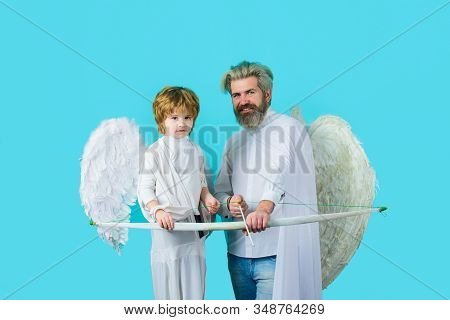 Father and son Angels. Father's day. Little cupid boy and father with bow and arrow. Happy father in angel costume with little son angel. Christmas angels. Cute angel. Gorgeous kid. Valentines day stock photo