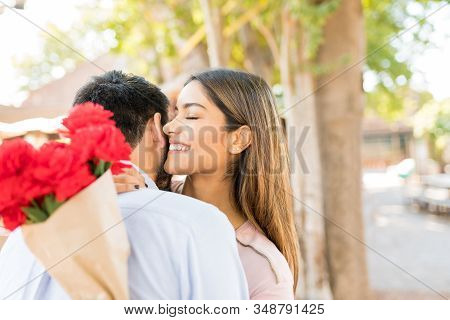 Smiling attractive young woman holding flowers while embracing boyfriend stock photo
