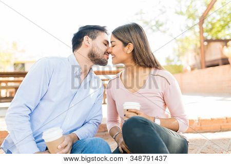 Affectionate couple kissing while sitting outside cafe during date stock photo