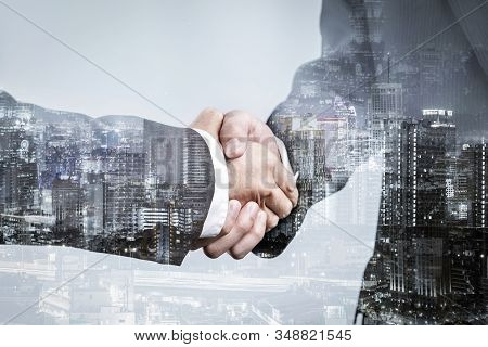Double exposure of business partnership handshake and modern city , Successful business greeting or agreement after perfect deal stock photo