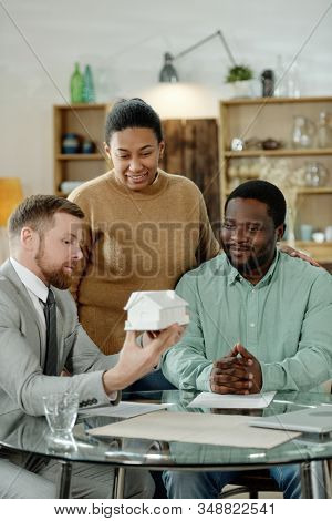 Professional financial accountant showing model of house to ethnic content couple having consultation stock photo