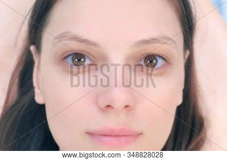 Portrait of young brunette woman looking at camera in cosmetology clinic before procedure, face closeup. She is lying on couch, waiting tint eyebrow cosmetic procedure in beauty clinic. stock photo