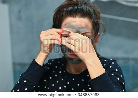 Girl puts patches on her eyes. The girl cares for her eyes. looking at the mirror glues patches for the eye. Eye care. Relieve eye fatigue. stock photo