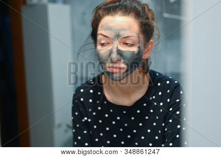 Bad morning, girl in front of the mirror. The girl takes care of her skin after a stormy night. Night party. After the disco. Stormy night. After a stormy night with friends. stock photo