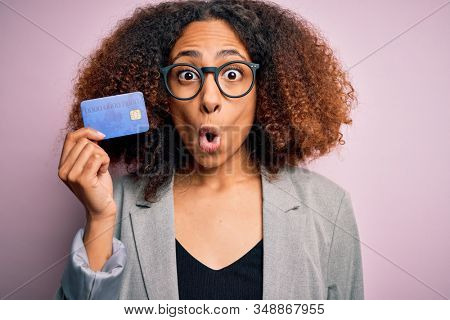 Young african american businesswoman with afro hair holding credit card over pink background scared in shock with a surprise face, afraid and excited with fear expression stock photo