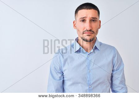 Young handsome business man standing over isolated background depressed and worry for distress, crying angry and afraid. Sad expression. stock photo