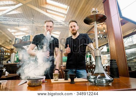 Hookah in the process preparations. Two young boys prepare hookah sisha in hookah bar, looking at camera. Tabaco preparation. stock photo