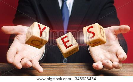 Cubes thrown by a man make up word YES. Agreement and acceptance, answer the question. Courage, irresistibility, zeal forwards, consent. Confirmation and approval. Important decision. Correct answer stock photo