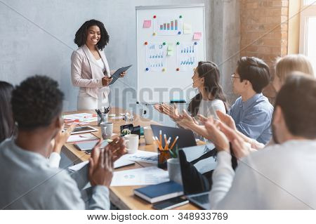 International business team applausing to black lady speaker, afro woman making business presentation, success concept stock photo