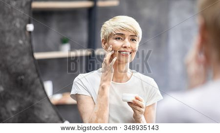 Anti-Aging Skincare. Beautiful Middle-Aged Woman Applying Facial Cream Standing In Bathroom. Panorama, Selective Focus stock photo