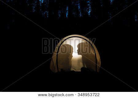 Silhouettes of children telling bedtime stories in tent at night during summer holidays camping in a forest stock photo