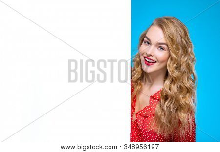 Young woman and a large white banner. Beautiful smiling girl is standing next to a Billboard. European  cheerful woman  stands next to advertising banner. Blonde girl and an empty ad sheet of paper. stock photo