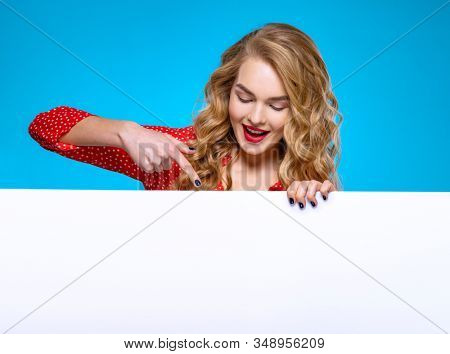 Young woman and a large white banner. Beautiful smiling girl is standing next to a Billboard. European woman points her finger at the text on advertising banner. Girl and an empty ad sheet of paper. stock photo