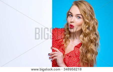 Expressive girl is standing next to a Billboard. Excited young woman and a large white banner.  European  cheerful woman  stands next to advertising banner. Blonde girl and an empty ad sheet of paper. stock photo