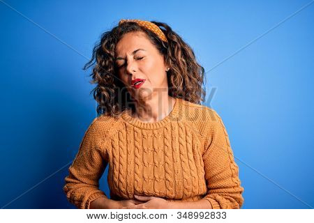Middle age beautiful woman wearing casual yellow sweater over isolated yellow background with hand on stomach because indigestion, painful illness feeling unwell. Ache concept. stock photo
