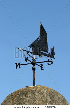 old black wrought iron weather vane of a ship design pointing west, set against a blue sky. stock photo