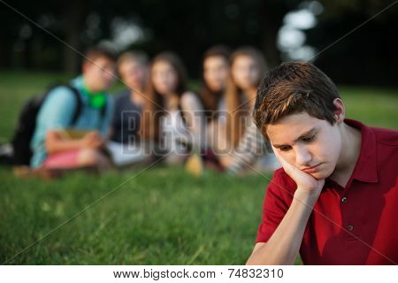 Sulking male caucasian teen with face in hands stock photo
