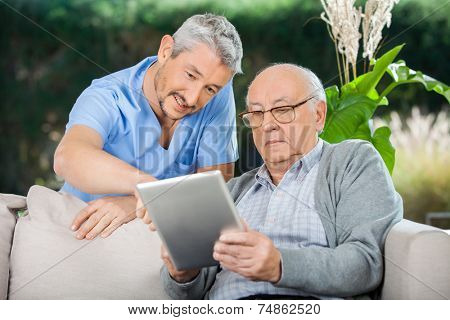 Male caretaker assisting senior man in using digital tablet at nursing home porch stock photo