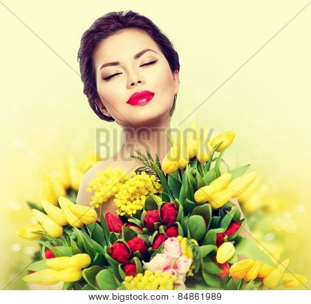 Beauty model Woman with Spring Flower bouquet. Beautiful girl with a Bouquet of colorful Tulip flowe