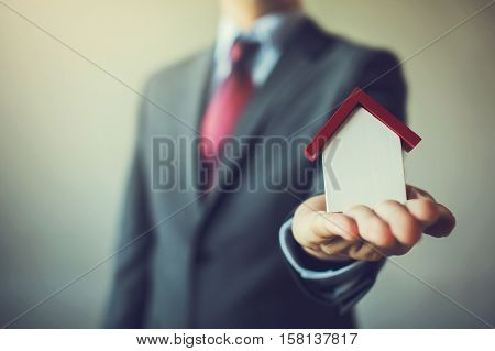 Business Man In Suit Having Miniature House On Palm Of His Hand - Business Mortgage, Property Loan,