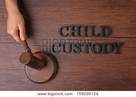 Hand holding court gavel and words CHILD CUSTODY on wooden background, top view stock photo