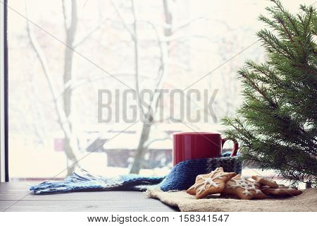 slide figure ginger cookies lying under a green tree on a background of mug and a winter window / warming atmosphere before Christmas