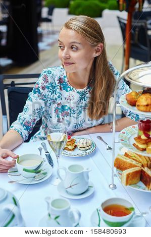 Beautiful young woman enjoying afternoon tea with selection of fancy cakes and sandwiches in a luxury Parisian restaurant stock photo