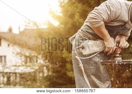 handyman working with grinding machine on a stone plate in the sunlight stock photo