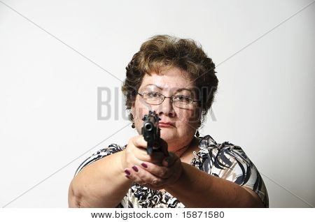 a mature woman with a serious look as she points a hand gun. stock photo