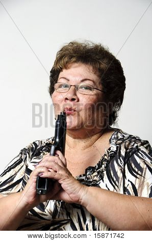 a mature woman blowing on the barrel of a beretta hand gun. stock photo