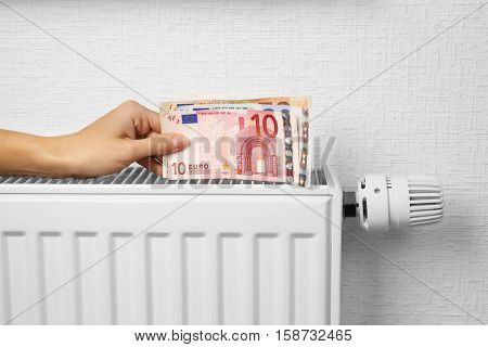 Woman holding money on heating battery background stock photo