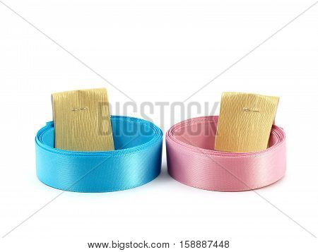close up two roll pastel colored ribbons (blue and pink) with gold paper label straps isolated on white background, prepare material for gift box wrapping and decoration stock photo