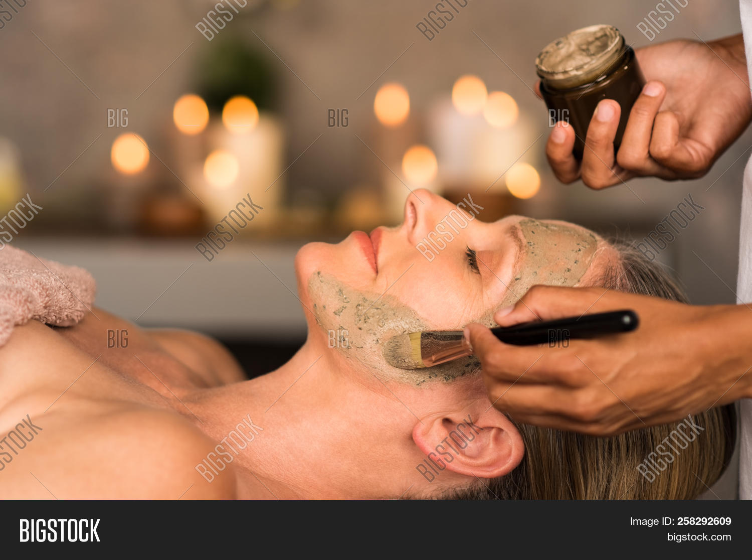 Senior woman relaxing while beautician getting purifying clay mask on her face. Closeup hand of mass