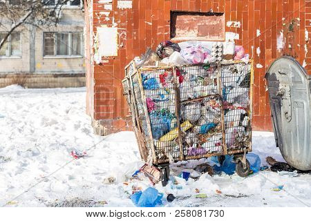 Overfilled waste container on city street. Garbage bin made of metal cage for plastic dump. Environment pollution . Plastic goods recycling stock photo