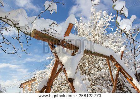 swing in winter, winter fairy tale in the yard, Snow-covered garden swing. wooden garden swing on chains stock photo