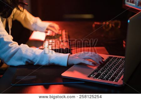 Woman working at home office hand on keyboard close up. Using both personal computer and laptop stock photo