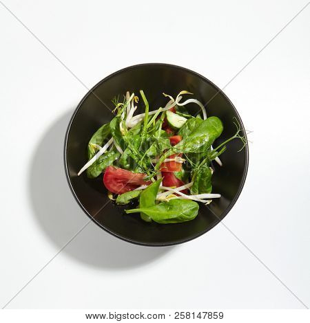 Macro Photo of Crunchy Vegetables Green Mix in Round Black Bowl Isolated on White Background. Restaurant Starter Menu with Sliced Tomatoes, Soybean Sprouts, Fresh Spinach Leaves and Young Pea Shoots stock photo