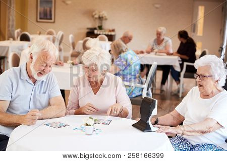 Senior Couple Being Served With Meal By Carer In Dining Room Of Retirement Home stock photo