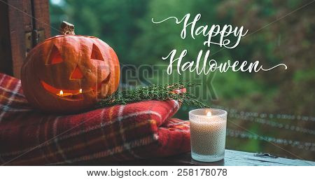 Background Halloween Pumpkin On A Cozy Window Sill With A Red Plaid. Whole Pumpkin And Sparkler Outd