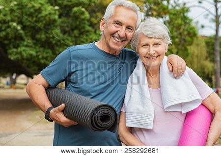 Lovely senior man and old woman holding yoga mat for exercising outdoor. Aged husband and wife ready