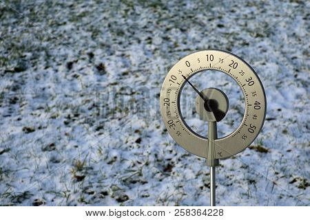 Big thermometer with celsius scale showing -5 degree placed in a frozen field with copy space stock photo
