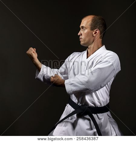 On a black background, the athlete performs the formal exercises of karate stock photo