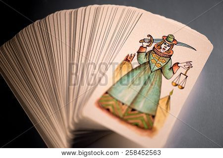 Pack of fanned out tarot cards with a pictorial Happiness card on top depicting a dancing couple stock photo