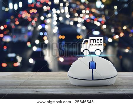 Free delivery truck flat icon with wireless computer mouse on wooden table over blur colorful night light city with cars in city, Business free delivery online concept stock photo