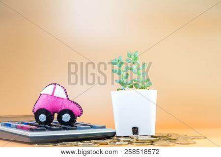 Car model put on the calculator and coin and cactus in the office, Loan and saving for buy a new car and investment a chattel in the future concept. stock photo