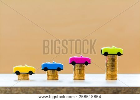 Stack coin with car model with growing on the top for collect interest put on the desk in the office, loan and saving for buy a new car and business investment a chattel in the future concept. stock photo