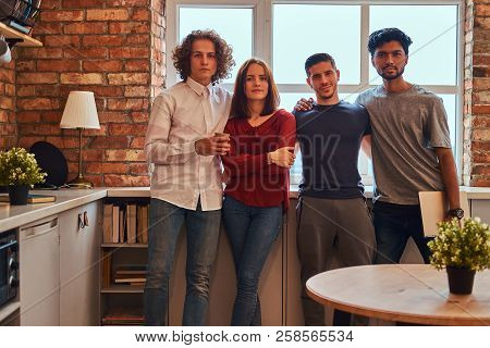 Group of interracial students with laptop in student dormitory. stock photo