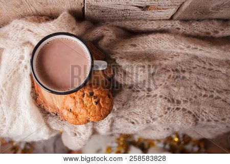 Cocoa with Cozy winter home background, cup of hot cacao with american cookies, warm knitted sweater on vintage wooden background, vintage tone, top vew, copy space. Lifestyle rustic nordic concept. stock photo