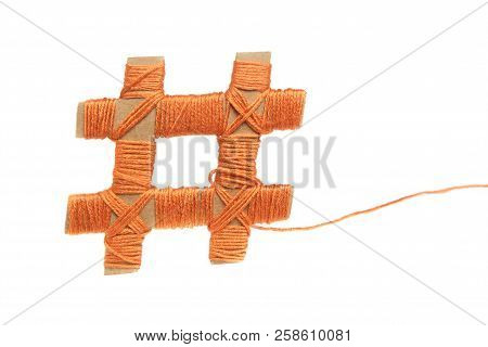 Hashtag made from cardboard and orange thread  isolated on white background. Number sign made from paper and cotton thread. stock photo
